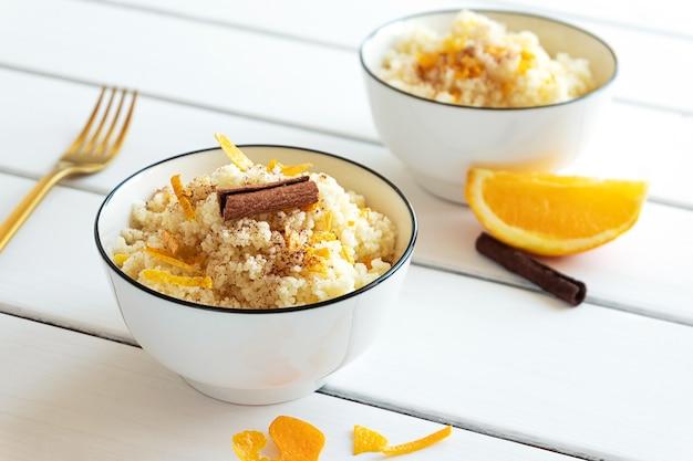 素朴な木製の背景にオレンジとシナモンのおいしい自家製クスクス。おいしいビーガンフード。