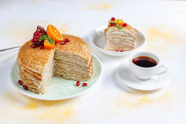 Вкусный домашний креповый торт, украшенный зернами граната и мандаринами.