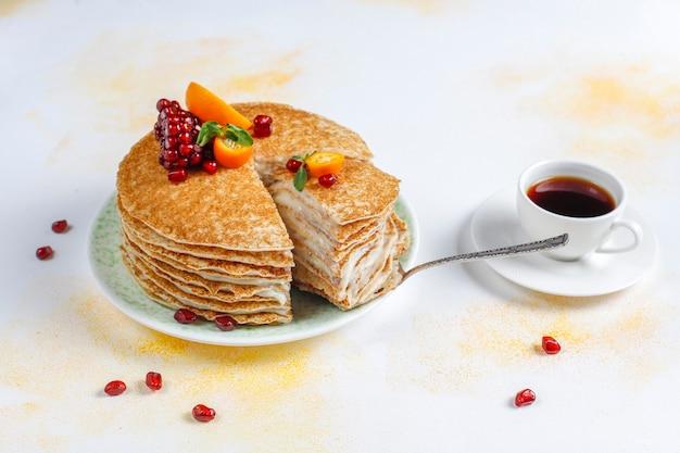 석류 씨와 만다린으로 장식 된 맛있는 수제 크레이프 케이크.