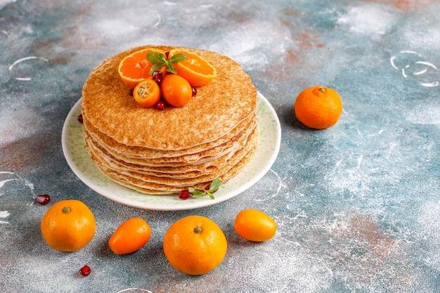 Deliziosa torta crepe fatta in casa decorata con semi di melograno e mandarini.