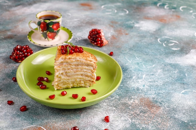 Delicious homemade crepe cake decorated with pomegranate seeds and mandarins.