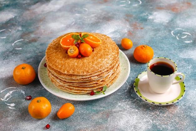 Deliziosa crepe fatta in casa decorata con semi di melograno e mandarini.