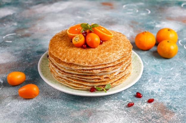 Deliziosa torta di crepe fatta in casa decorata con semi di melograno e mandarini.