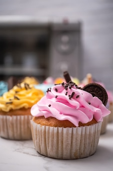 Вкусные домашние кексы с разноцветным кремом и начинкой с конфетами и шоколадным печеньем.