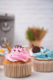 다채로운 크림과 사탕과 초콜릿 쿠키 토핑 맛있는 수제 컵 케이크.