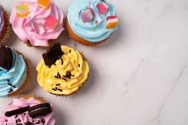 다채로운 크림과 사탕과 초콜릿 쿠키를 얹은 맛있는 수제 컵 케이크