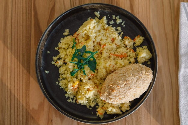 Delicious homemade cutlets, couscous with vegetables and arugula.