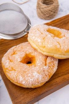 おいしい自家製ドーナツまたはドーナツドーナツは多くの国で人気があり、自家製またはパン屋のスーパーマーケットで購入できる甘いスナックとしてさまざまな形で準備されています