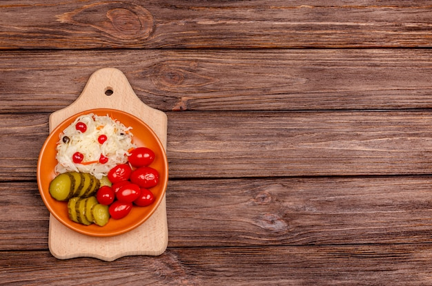 Delicious homemade fermented vegetables on a plate sauerkraut, pickled tomatoes, pickles, wooden background