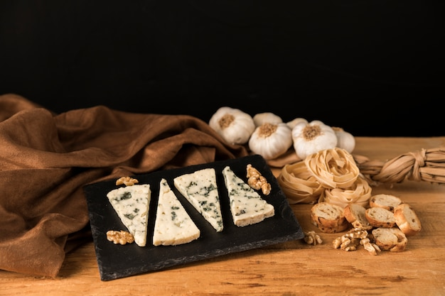 Delicious homemade food with cheese slices and walnut on stone over background