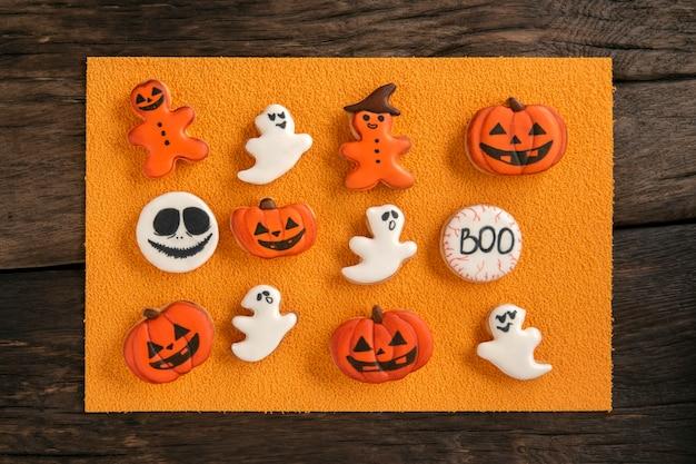 オレンジ色の背景にハロウィーンのためのおいしい自家製生姜クッキー。生姜クッキーの絵文字、男、カボチャ、幽霊