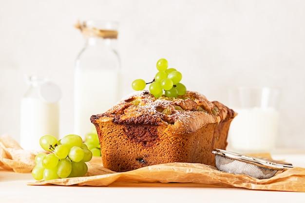 Вкусный домашний торт из виноградной лепешки с тимьяном и сахарной пудрой на пергаментной бумаге.
