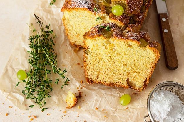 羊皮紙の紙にタイムと砂糖の粉でおいしい自家製ブドウのパンのケーキ。