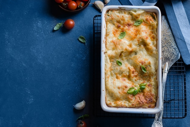 Delicious homemade lasagne with ricotta cheese and spinach on blue stone concreet table background. vegetarian food. italian food. top view with copy space