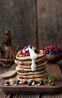 Delicious homemade pancakes, fritters with sour cream  and fresh forest berries