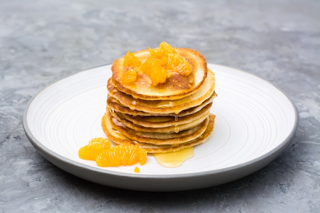 Delicious homemade pancakes with tangerines and honey on a plate on the table
