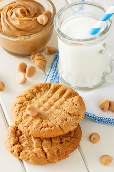 우유의 찻잔으로 맛있는 수 제 땅콩 버터 쿠키. 흰색 나무 공간. 건강 간식 또는 맛있는 아침 식사 개념.