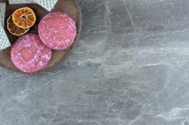 Deliziosi biscotti rosa fatti in casa con fette di limone secche sul piatto di legno.