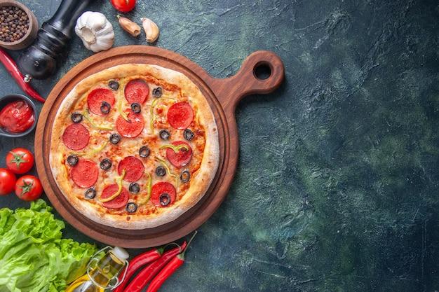 暗い面の右側にある、木製のまな板にトマト、ケチャップ、緑の束、ニンニクを載せたおいしい自家製ピザ