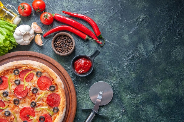 Deliziosa pizza fatta in casa su tavola di legno pomodori ketchup garlics pepe olio bottiglia fascio verde su superficie scura in primo piano