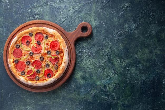 Deliziosa pizza fatta in casa su tagliere di legno sul lato destro su superficie scura isolata