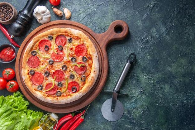 Deliziosa pizza fatta in casa su tagliere di legno pomodori aglio ketchup fascio verde bottiglia di olio pepe su superficie scura in primo piano