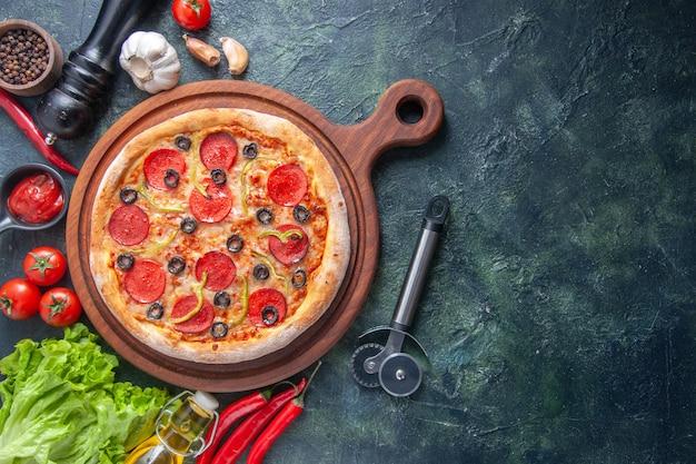 Deliziosa pizza fatta in casa su tagliere di legno pomodori ketchup aglio verde bottiglia di olio sul lato destro su superficie scura