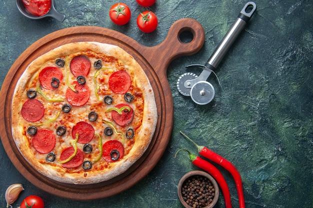 Deliziosa pizza fatta in casa su tagliere di legno e pomodori ketchup all'aglio pepe su superficie scura isolata