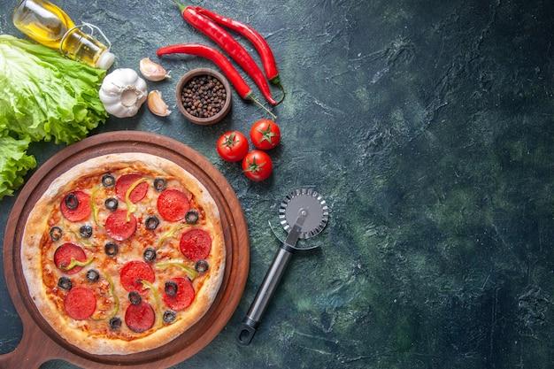 Deliziosa pizza fatta in casa su tagliere di legno pomodori ketchup garlics pepe olio bottiglia verde fascio su superficie scura