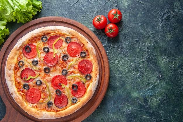 Deliziosa pizza fatta in casa su tagliere di legno pomodori ketchup fascio verde su superficie scura
