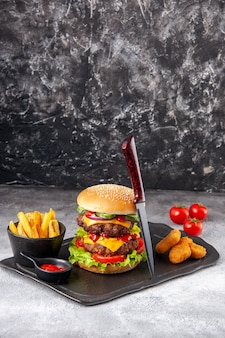 おいしい自家製サンドイッチとチキン ナゲット フライ ケチャップ フォーク、グレーの氷の表面に茎を持つブラック ボード トマト