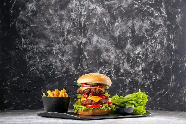 Вкусный домашний бутерброд и кетчуп с вилкой, обжаренный зеленым на черном подносе на серой проблемной изолированной поверхности со свободным пространством