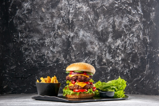 Delicious homemade sandwich and fork ketchup fries green on black tray on gray distressed isolated surface with free space