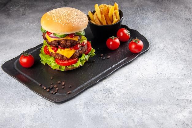 Delizioso panino fatto in casa e patatine fritte ketchup su lavagna nera sul lato destro sulla superficie grigia del ghiaccio ice