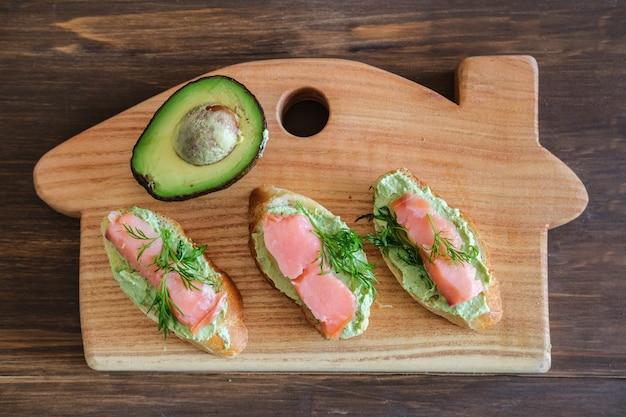 Вкусные домашние бутерброды с авокадо и лососем на деревянной разделочной доске, вид сверху