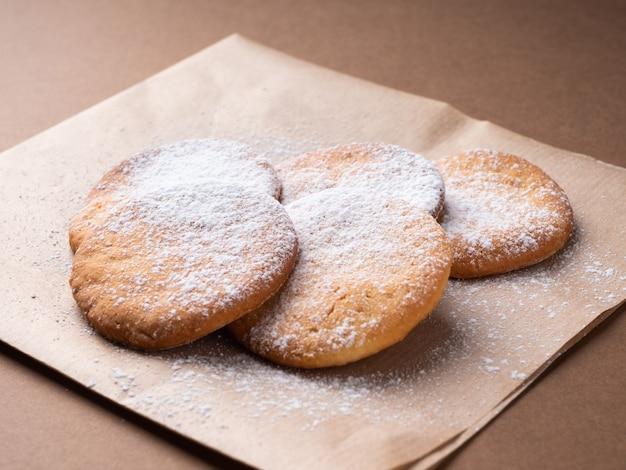 따뜻한 갈색 톤, 근접에서 맛있는 수 제 치즈, 아몬드 쿠키. 종이 냅킨에 가루 설탕 쿠키.