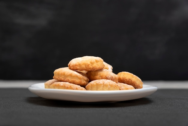Вкусный домашний песочный пирог на белой тарелке, черной поверхности. вид сбоку. свежее песочное печенье.