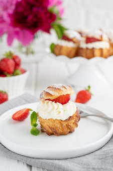 Delicious homemade small cakes profiterole choux pastry with custard, strawberry and icing powder