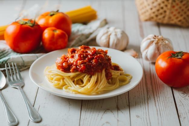 Вкусные домашние макаронные изделия спагетти с томатным соусом и фаршем служили на белой тарелке с ингредиентом на белом деревянном фоне. итальянская еда. домашняя еда.