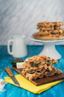 Delicious homemade spicy waffle on wooden chopping board
