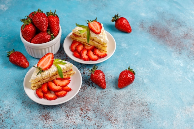 Delicious homemade strawberry cake slices with cream and fresh strawberries, top view