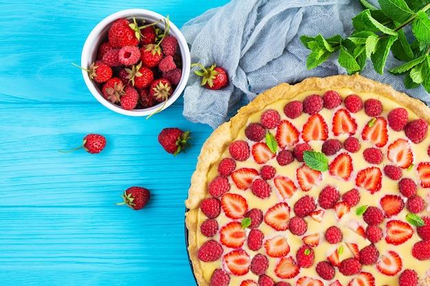 青い木製の背景にイチゴとラズベリーを添えたミントの葉を添えたおいしい自家製タルト。上面図