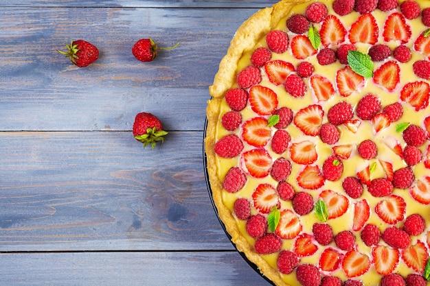 木製の背景にイチゴとラズベリーを添えたミントの葉を添えたおいしい自家製タルト。上面図