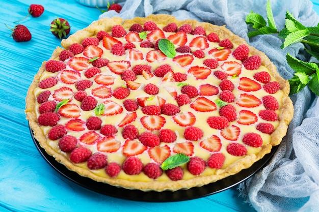 木製の背景にイチゴとラズベリーを添えたミントの葉とおいしい自家製タルト