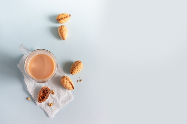 Delicious homemade walnut cookies in a bowl and hot coffee on blue background with copy space.