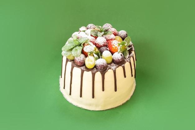 孤立した背景の上の果物とおいしい自家製ホワイトチョコレートケーキ