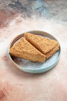 Вкусный медовый торт внутри подноса на сером