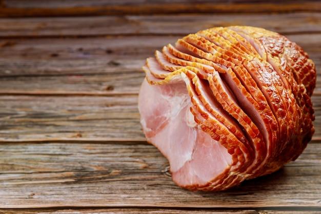 Вкусный мед, копченый свиной окорок на деревенском деревянном фоне.