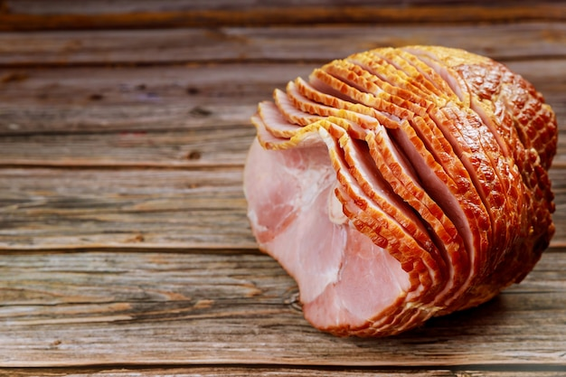 Delicious honey smoked pork ham on rustic wooden background.