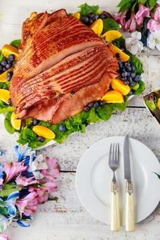 Вкусный мед, копченый свиной окорок со столом на белом деревянном фоне.